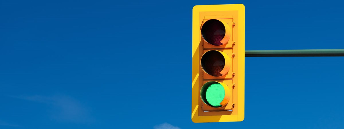 green traffic light with a blue sky in the background